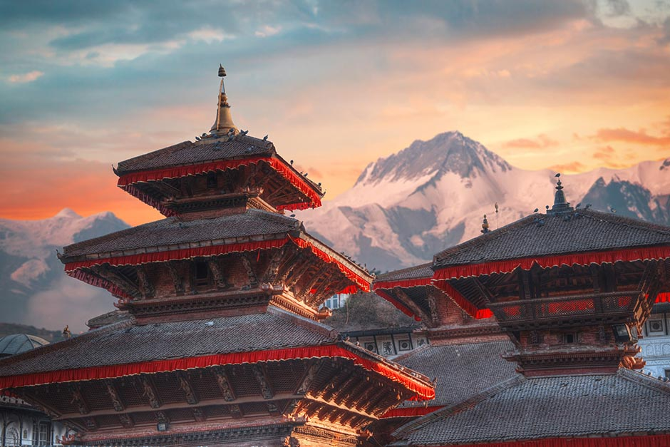 ancient styled buildings overlooking snowy mountains in Nepal